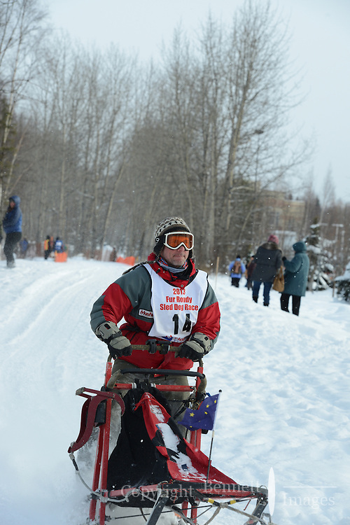 Greg Sellentin passes by University Lake during the first day of the World Championship Sled Dog Races, a highlight of the 2013 Anchorage, Alaska, Fur Rendezvous.