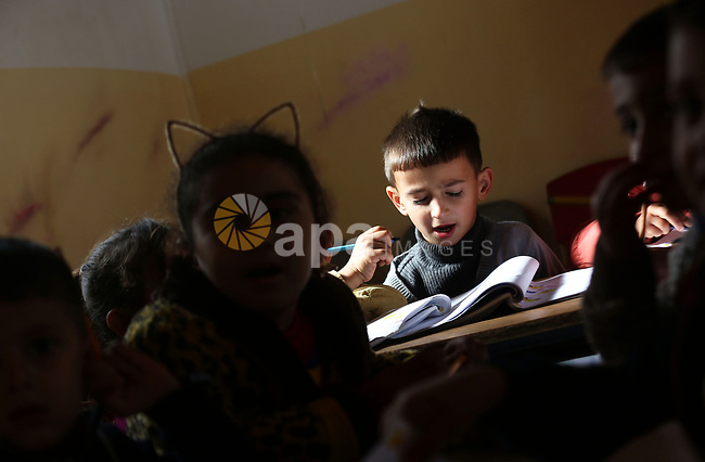 Palestinian schoolchildren attend a lesson after Israeli troops confiscated caravans used as school classrooms, due to the lack of an Israeli-issued construction permit, at Ghassan Kanafani Kindergarten in the West Bank village of Furosh Beit Dajan, east  Nablus, on December 11, 2019. Photo by Shadi Jarar'ah