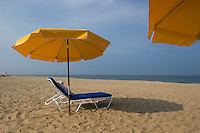Lounge chair sits under umbrella on beach