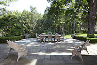 The stone-flagged terrace is used for outdoor dining and overlooks the garden