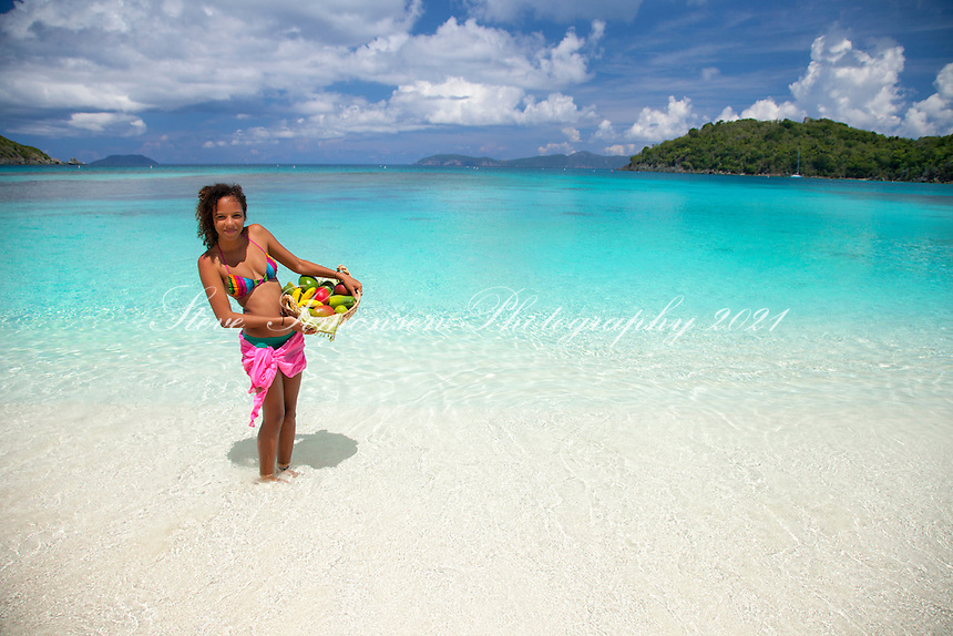 Young woman on the beach with a basket of fruit<br />