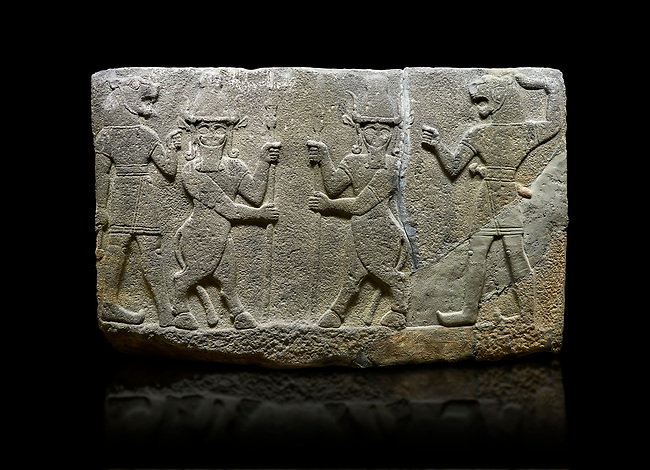 Photo of Hittite relief sculpted orthostat stone panel of Herald's Wall. Basalt, Karkamıs, (Kargamıs), Carchemish (Karkemish), 900-700 B.C. Anatolian Civilisations Museum, Ankara, Turkey.<br /> <br /> Protective mixed creatures. One each hand of the lion-headed men is in the form of a fist. The mace on the left is over the head of the weapon on the right. The two bull-men in the middle carry one spear each in their hands. Bull-man is known as Kusarikku, and the lion-man is known as Ugallu. <br /> <br /> Against a black background.
