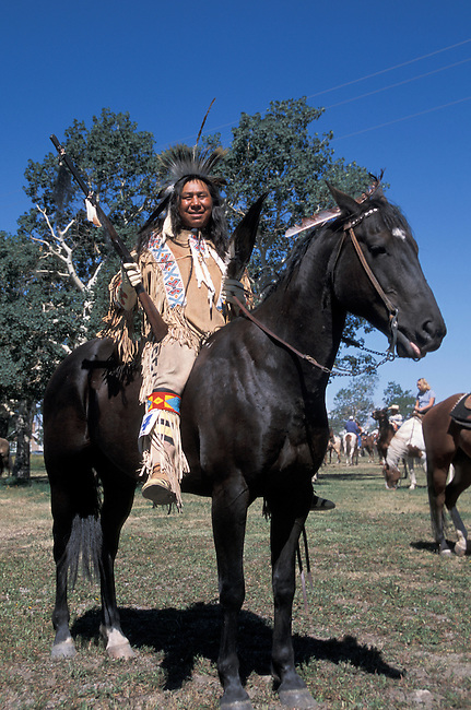 Blackfeet man and tribal member Aarie Mad Plume dressed in traditional regalia of beaded buckskin clorhing holds a coup stick rifle while on his horse bareback during a parade in Browning Montana