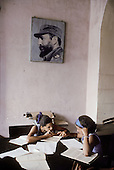 Two schoolgirls studying in a public library in Cienfuegos, beneath a picture of Fidel Castro.