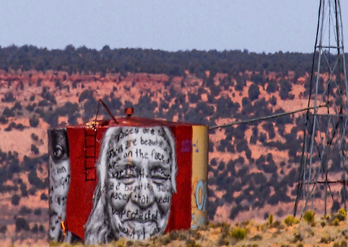 An Indian Face along with some wrtings appear on a water tank in rural Northern Arizona