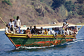Lake Tanganyika, Tanzania. Pedestrian ferry boat painted green, red and yellow with two black umbrella sunshades.