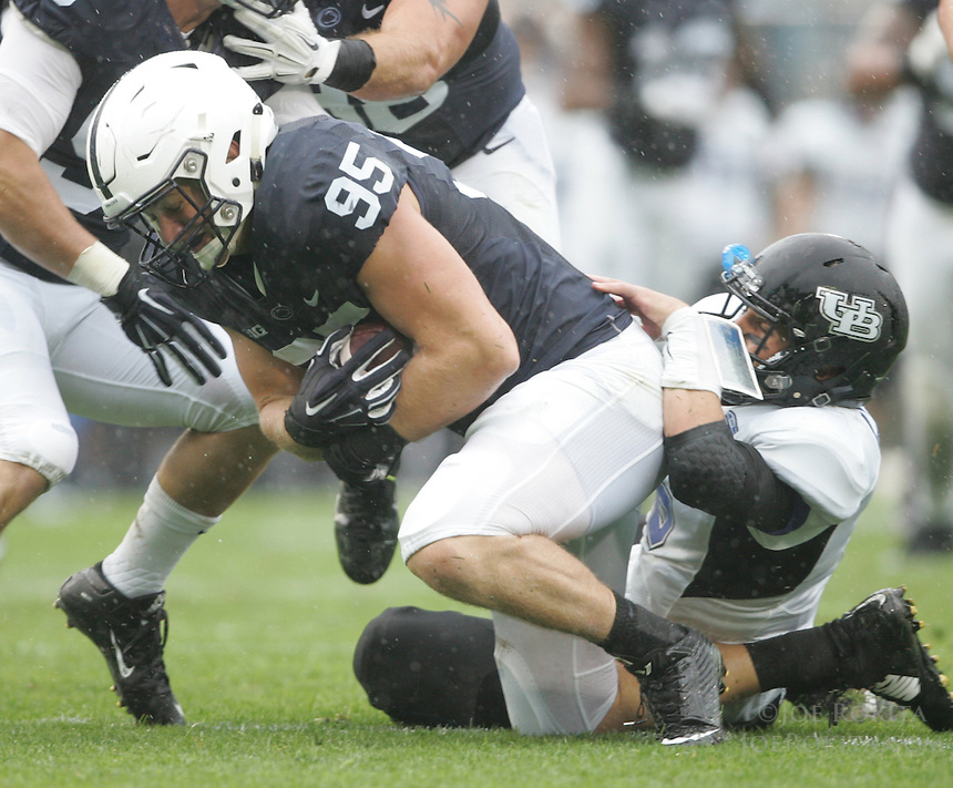 State College, PA - 09/12/2015:  DE Carl Nassib is tackled by the Buffalo QB Joe Licata after intercepting a Licata pass. Penn State defeated Buffalo by a score of 27-14 at rainy Beaver Stadium in University Park, PA.<br /> <br /> Photos by Joe Rokita / JoeRokita.com