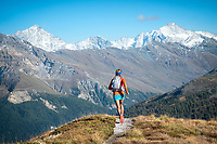 Running on the Via Valais, a multi-day trail running tour connecting Verbier with Zermatt, Switzerland. A woman runs towards the distant big mountains, where she is headed as part of the tour.