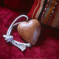 A close up of a wooden heart resting on a red seat