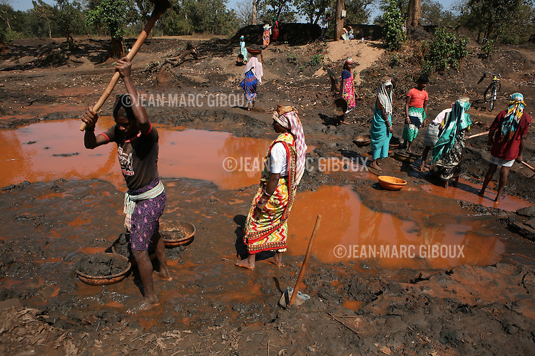 """KIRANDUL, DANTEWARA DISTRICT, CHHATTISGARH, INDIA, FEBRUARY 29, 2008 :  Kirandul is the center of Iron mining in Dantewara district, the ground is rich with high quality iron ore. The mines are operated by NMDC (...) and the ore powder is then mixed with water and pumped into a 265 km long pipeline to the coast, to be processed in Gujarat. Of these 265 km, 67 are controlled by the Naxalites, the Maoist insurgents that has been waging a war against the Indian government for the past 25 years and has been gaining momentum in in the past few years. They fights for the rural poor like the Gond tribals who are afraid to loose their land to mining and development. They are present in some 150 of the 600 districts of India, and Dantewara is one of Chhattisgarh rural Maoist stronghold where they control most of the countryside. The overwhelmed police force is hiring more personel to deal with the Naxalite threat and the Government has armed civil defence anti-naxalite milicias to take on the rebels , emptying villages to cut local support to the rebels. The movement called """"Salwa Judum"""" (campaign for peace)  started in june 2005 when some villages took a stand against the Maoists, but it is now dragging the whole district into the bloody civil war, at the expense of the  local tribal villagers caught in the middle and forced to leave their ancestral homes for the security of refugee camps. The conflict has claimed over 900 lives in 2006 and again in 2007, and some 50 to 60,000 people live in makeshift camps, protected by the Salwa Judum and the police force. But for the tribals who do not want to leave their home and villages, there are no government services available, meaning no health care or education for the children. They live in complete isolation from the rest of India. (Photo by Jean-Marc Giboux/ GettyImages)KIRANDUL, DANTEWARA DISTRICT, CHHATTISGARH, INDIA, FEBRUARY 29, 2008 :  Laborers collect iron ore in the runoff of the river that flow from the Kirandul NMDC m"""