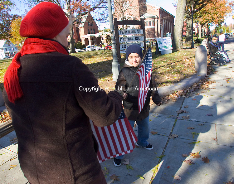 NAUGATUCK, CT- 11 NOV 2007- 111107JT04- <br /> Geri Stotz gives Daniel Pagan, Jr., 8, one of 400 flags that she and Army veteran Fran Keith were giving to children for Sunday's Veterans Day ceremony at the Naugatuck Green. <br /> Josalee Thrift / Republican-American