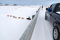 Martin Buser runs under the bridge on the Kouwegok slough as locals take photos shortly after he left the Unalakleet checkpoint on Monday  afternoon March 12th during the 2018 Iditarod Sled Dog Race -- Alaska<br /> <br /> Photo by Jeff Schultz/SchultzPhoto.com  (C) 2018  ALL RIGHTS RESERVED
