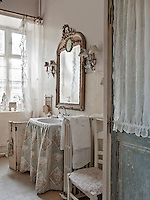 The corner of a bathroom decorated in neutral and grey. A mirror hangs above a washbasin, which is draped around with a fabric cover.