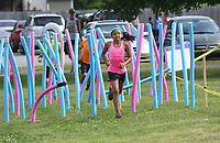 """NWA Democrat-Gazette/FLIP PUTTHOFF <br /> OBSTACLE RUNAROUND<br /> Kids run through a noodle maze on Saturday June 9 2018 during the Obstacle Runaround at the Jones Center for Families in Springdale Youngsters age 5-12 took part in the one-mile run with 15 obstacles on the course including a slip and slide, belly crawl, and water balloon toss. """"It's our version of a mud run for kids,"""" said Stephen Paul with the Jones Center."""