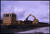 3/4 right-front view of Herzog control flat and ballast train with backhoe loading cars from hoppers on adjacent track.  &quot;Track Train - Loader Runs Back and Forth on Rails on Top of Gondolas&quot;.<br /> Herzog  Monte Vista, CO  Taken by Berkstresser, George - 3/2003