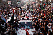 Punjab, Pakistan<br /> November 12, 1988<br /> <br /> Benazir Bhutto arrives at a massive campaign rally in the Punjab province.<br /> <br /> Benazir Bhutto is the eldest child of former Pakistan President and Prime Minister Zulfikar Ali Bhutto. She found herself placed under house arrest in the wake of her father's imprisonment and subsequent execution in 1979. In 1984 she became the leader in exile of the Pakistan Peoples Party (PPP), her father's party, though she was unable to make her political presence felt in Pakistan until after the death of General Muhammad Zia-ul-Haq. <br /> <br /> On 16 November 1988 Benazir's PPP won the largest bloc of seats in the National Assembly. Bhutto was sworn in as Prime Minister in December, at age 35 she became the first woman to head the government of a Muslim-majority state in modern times. <br /> <br /> She was removed from office 20 months later under orders of then-president Ghulam Ishaq Khan for alleged corruption. Bhutto was re-elected in 1993 but was again removed by President Farooq Leghari in 1996, on similar charges. Bhutto went into self-imposed exile in Dubai in 1998, until she returned to Pakistan on October 2007, after General Musharraf granted her amnesty and all corruption charges withdrawn.