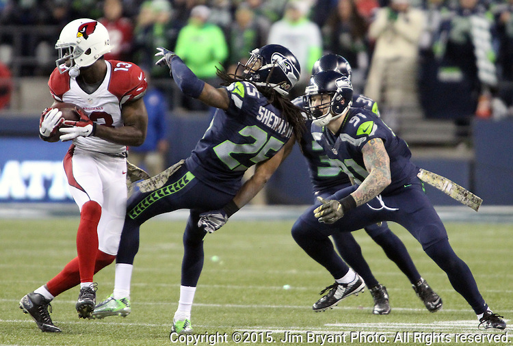 Arizona Cardinals wide receiver Michael Floyd (15)  catches a pass over Seattle Seahawks defensive end Cassius Marsh (91), Cornerback Richard Sherman (25) and strong safety Kam Chancellor (31) at CenturyLink Field in Seattle, Washington on November 15, 2015. The Cardinals beat the Seahawks 39-32.   ©2015. Jim Bryant photo. All Rights Reserved.