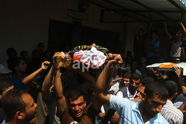 Palestinian mourners carry the body of Anwar Isleem, a commander in the Islamic Jihad militant during his funeral in Bureij Refugee Camp in central Gaza Strip on August 20, 2011 Anwar Isleem and Emad Abu Aabdeh were killed during an Israeli airstrike in response to militant rockets. Photo by Ashraf Amra