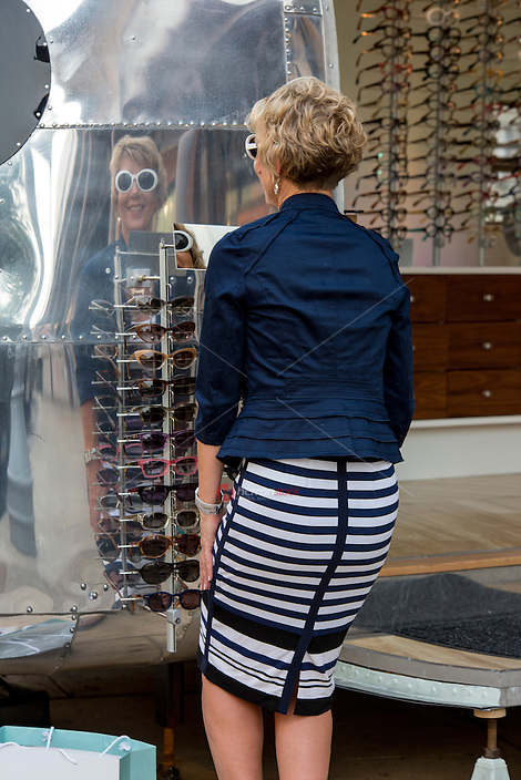 Mirror reflection of an attractive female shopper trying on sunglasses at an Austin outdoor shopping mall