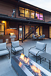 Patio area with outdoor dining table, grill area, and firepit with comfortable seating