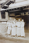 rowdy males in yukata with sake bottles in front of an Ryokan hotel early 1950s