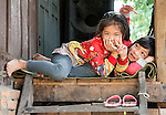 Two young Lao girls on the side of a street in Luang Prabang have fun making faces for my camera.