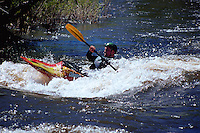 A kayaker navigates rapids in a fast-running stream. Steamboat, Colorado.