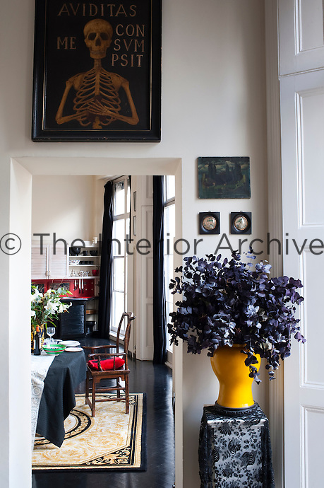 A cheerfully sepulchral corner has been created in the living room with black foliage, black lace and a macabre painting of a skeleton