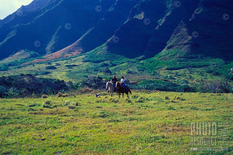 Couple riding horses near the majestic Koolau Mountains at Kualoa Ranch, on Oahu's windward coast