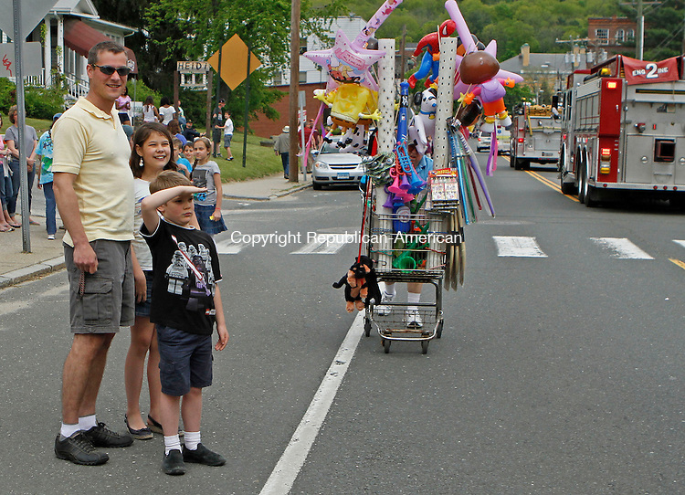 Winsted, CT-051813MK25 Joseph Giumasro salutes the Winsted firemen as his father Bob and sister Sofia look on during the 76th annual pet parade on Main St. in Winsted on Saturday afternoon. Hundreds of people gathered along the route to cheer on the participants, pets and honorees. Michael Kabelka Republican American