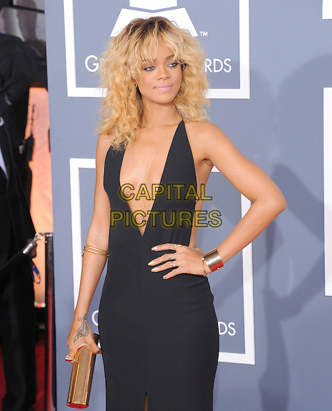 Rihanna (wearing Giorgio Armani).The 54th Annual GRAMMY Awards held at the Staples Center, Los Angeles, California, USA..February 12th, 2012.half length black dress plunging neckline cleavage hand on hip silver gold clutch bag cuff bracelet tattoo blonde hair.CAP/RKE/DVS.©DVS/RockinExposures/Capital Pictures.