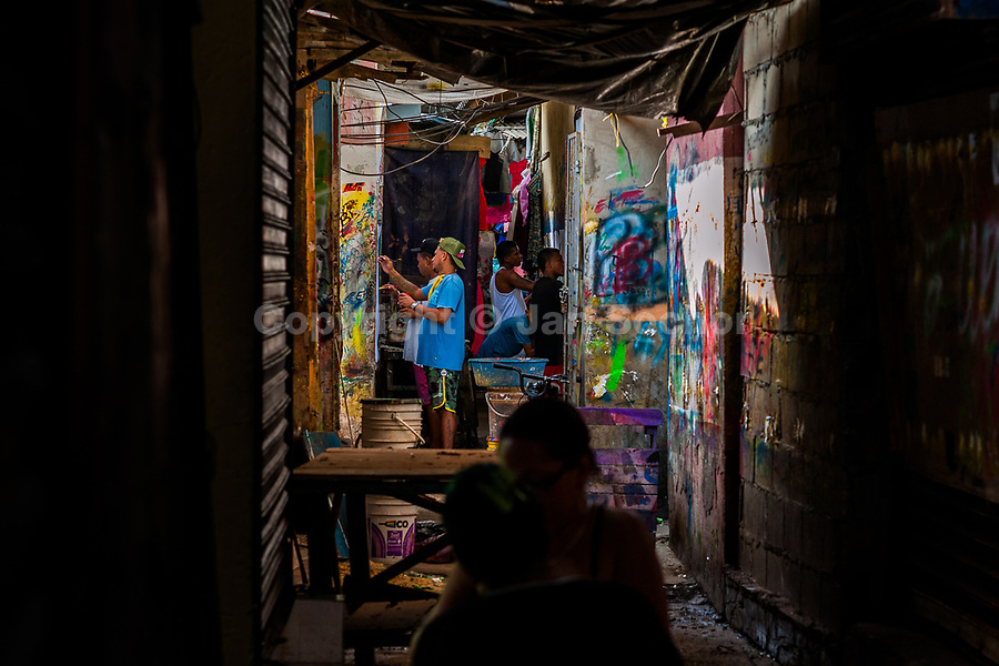 """Colombian sign painter work on music party posters in the sign painting workshop in Cartagena, Colombia, 11 December 2017. Hidden in the dark, narrow alleys of Bazurto market, a group of dozen young men gathered around José Corredor (""""Runner""""), the master painter, produce every day hundreds of hand-painted posters. Although the vast majority of the production is designed for a cheap visual promotion of popular Champeta music parties, held every weekend around the city, Runner and his apprentices also create other graphic design artworks, based on brush lettering technique. Using simple brushes and bright paints, the artisanal workshop keeps the traditional sign painting art alive."""