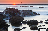 A long-exposure shot taken during sunset at Little Corona beach in Corona Del Mar (Newport Beach), CA.  The sun is setting over the entrance to Newport Pier while water cascades over an intertidal rock visible in the foreground.