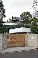 The entrance of the modern eco house with stone walls and sliding entrance door.