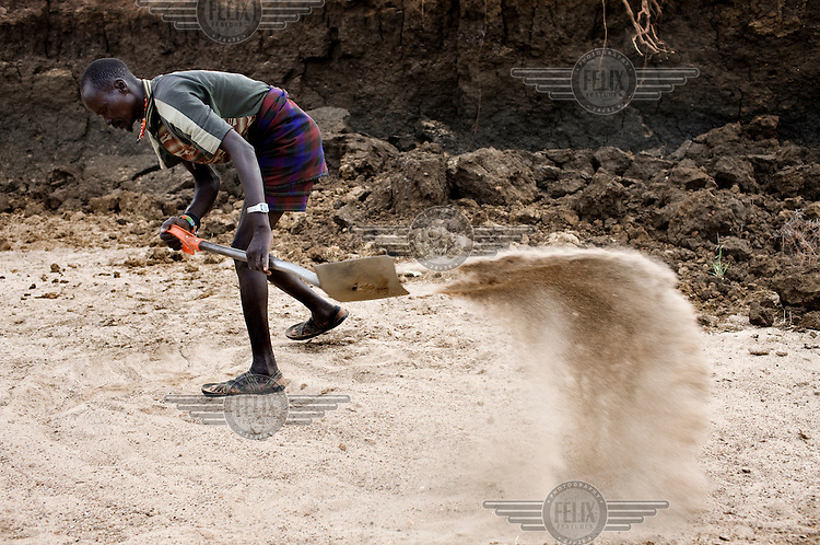 A man digs for a water source in a dried out river bed.