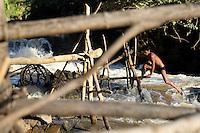 A fisherman is climbing traps to get through a channel at Khom Pa Sai falls, Khone falls, Laos-2010