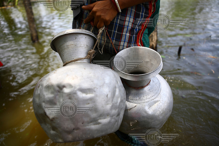 A villager carries waterjugs. There are severe clean water shortages as floodwater becomes stagnant and polluted, contaminating existing water supplies. Thousands of people were displaced in Shyamnagar Upazila, Satkhira district after Cyclone Aila struck Bangladesh on 25/05/2009, triggering tidal surges and floods..
