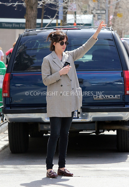 WWW.ACEPIXS.COM<br /> <br /> April 15 2015, New York City<br /> <br /> Actress Dakota Johnson grabs a cab outside her apartment on April 15 2015 in New York City<br /> <br /> By Line: Philip Vaughan/ACE Pictures<br /> <br /> ACE Pictures, Inc.<br /> tel: 646 769 0430<br /> Email: info@acepixs.com<br /> www.acepixs.com
