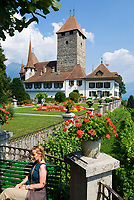CHE, Schweiz, Kanton Bern, Berner Oberland, Spiez: Schloss Spiez am Thunersee - Frau sitzt auf Bank | CHE, Switzerland, Bern Canton, Bernese Oberland, Spiez: castle Spiez at Lake Thun - woman sitting on bench