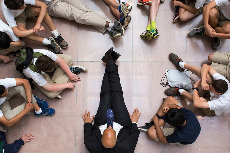 UNITED STATES - MAY 24 - Sen. Cory Booker, D-N.J., sits on the floor as he meets with 8th graders from Princeton Academy of the Sacred Heart on their end of year trip to Washington, in the atrium of the Hart Senate Office Building, in Washington, Tuesday, May 24, 2016. In an unofficial right of passage, thousands of middle school students visit the nation's capital each year after after studying the United States history in school. (Photo By Al Drago/CQ Roll Call)