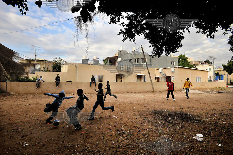 Youth play soccer near their temporary shelter, where they live amongst an Eritrean asylum seeker community.