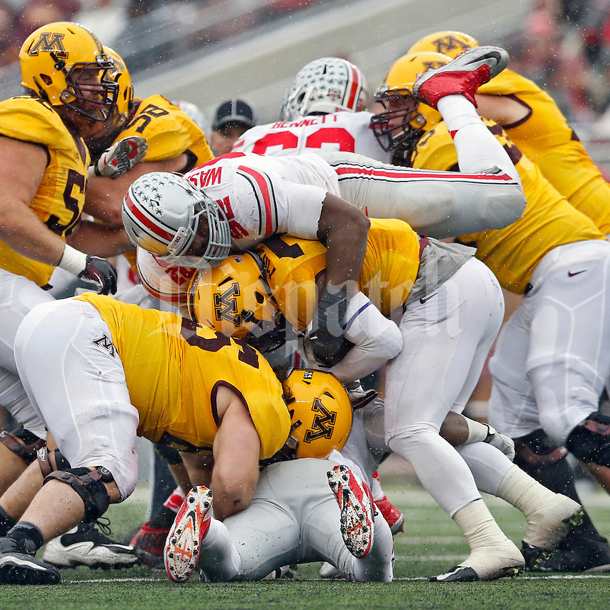 Ohio State Buckeyes defensive lineman Adolphus Washington (92) tackles Minnesota Golden Gophers running back David Cobb (27) during the 3rd quarter at TCF Bank Stadium in Minneapolis, Minn. on November 15, 2014.  (Dispatch photo by Kyle Robertson)