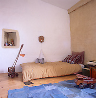 A simple, child's bedroom with neutral stone walls. A bed in the corner has a striped cover and pillow and a blue rug on the floor is made from denim fabric squares.