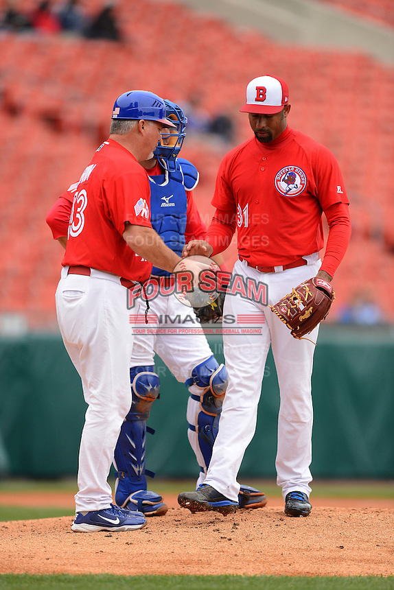 Buffalo Bisons pitcher Miguel Batista #31 hands the ball to manager Marty Brown during a pitching change as catcher Mike Nickeas looks on during a game against the Norfolk Tides on May 9, 2013 at Coca-Cola Field in Buffalo, New York.  Norfolk defeated Buffalo 7-1.  (Mike Janes/Four Seam Images)