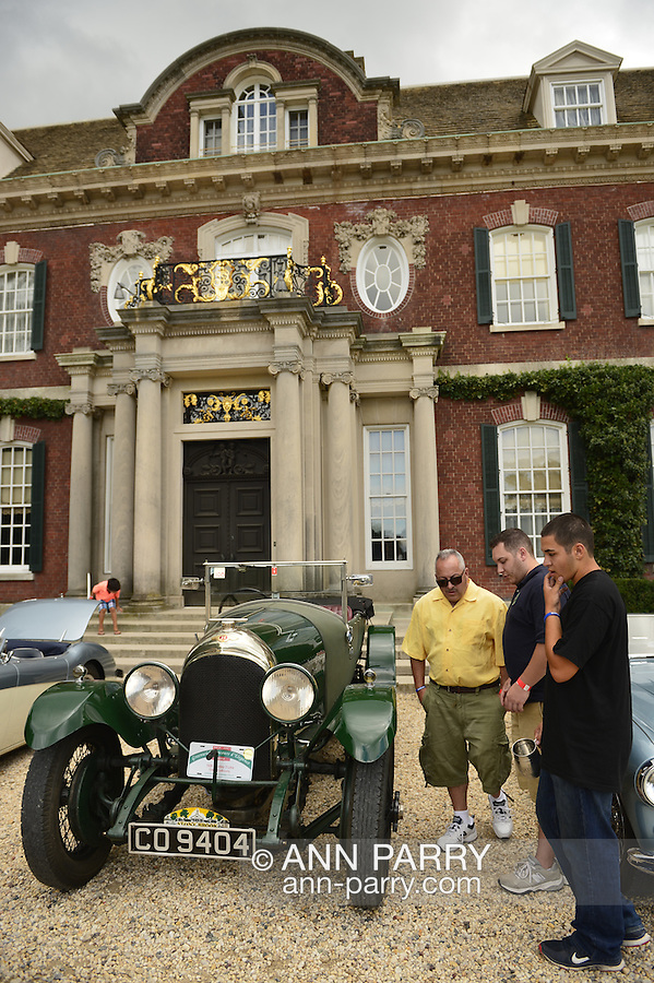 Old Westbury, New York, U.S. - August 23, 2014 - Visitors are looking at a green Bentley 1926 3 Liter historic luxury car, owner Edward LaBounty, parked in front of the mansion at the 54th Annual Long Island Scottish Festival and Highland Games, co-hosted by L. I. Scottish Clan MacDuff, at Old Westbury Gardens on Long Island's Gold Coast..