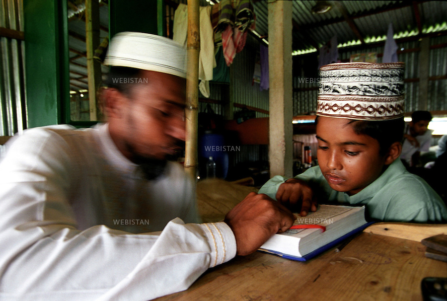 2005..Bangladesh. In a madrassa, a Muslim pupil studies with his teacher. .Bangladesh. Dans une madrassa, un élève musulman étudie avec son professeur.