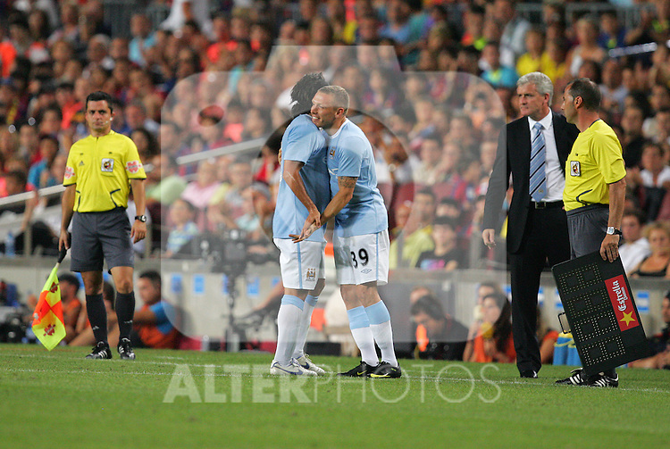 Carlos Tevez embraces with Craig Bellamy during the Joan Gamper Trophy match between Barcelona and Manchester City at the Camp Nou Stadium on August 19, 2009 in Barcelona, Spain. Manchester City won the match 1-0.
