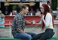 NWA Democrat-Gazette/ANDY SHUPE<br /> Zachary Elkins (left) of Fayetteville smiles Friday, Aug. 9, 2019, as his girlfriend, Lisa Anderson of Rogers, takes a bite as they share a grape ice cream during the 121st Tontitown Grape Festival in Tontitown. The festival, which features crafts vendors, chicken and spaghetti dinners and a midway, continues through today.