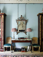 The sitting room is decorated in a cool blue with traditional furnishings in a pleasing symmetry. Tall bookcases and cane-backed chairs stand either side of a marble-topped Georgian console table.