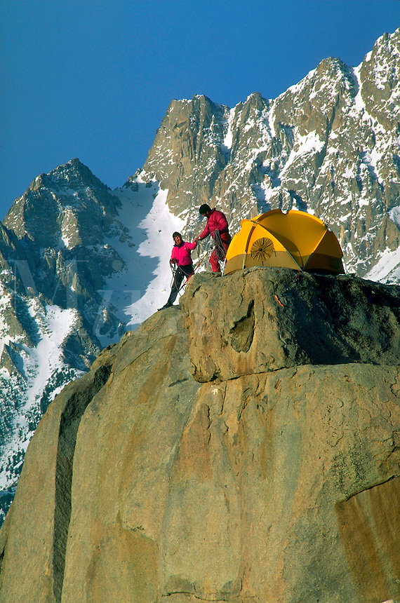 Two climbers setting up a winter camp on a rock peak below Basin Mountain, Eastern Sierra, California.